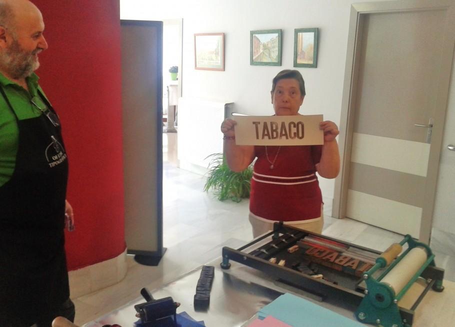 Una de las residentes muestra la palabra que ha impreso